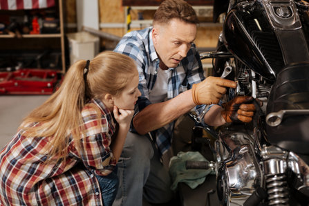 Father teaches his daughter about mechanics.