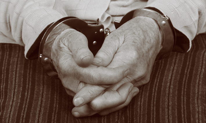 A senior citizen in handcuffs.